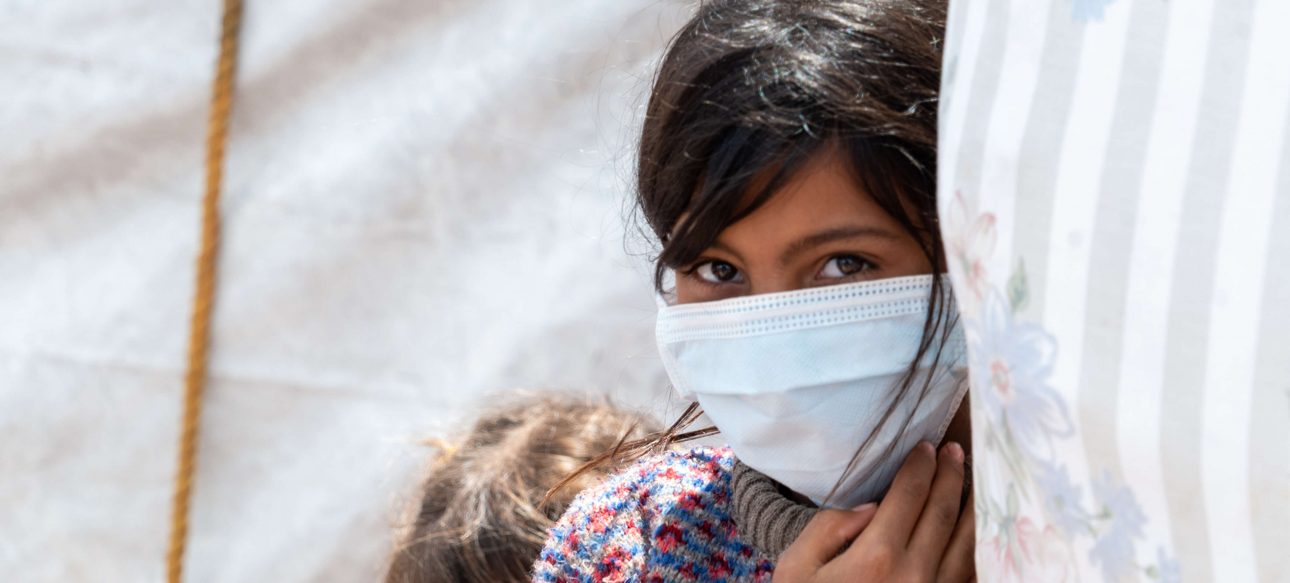 9 year old Bushra wearing a mask provided by Islamic Relief
